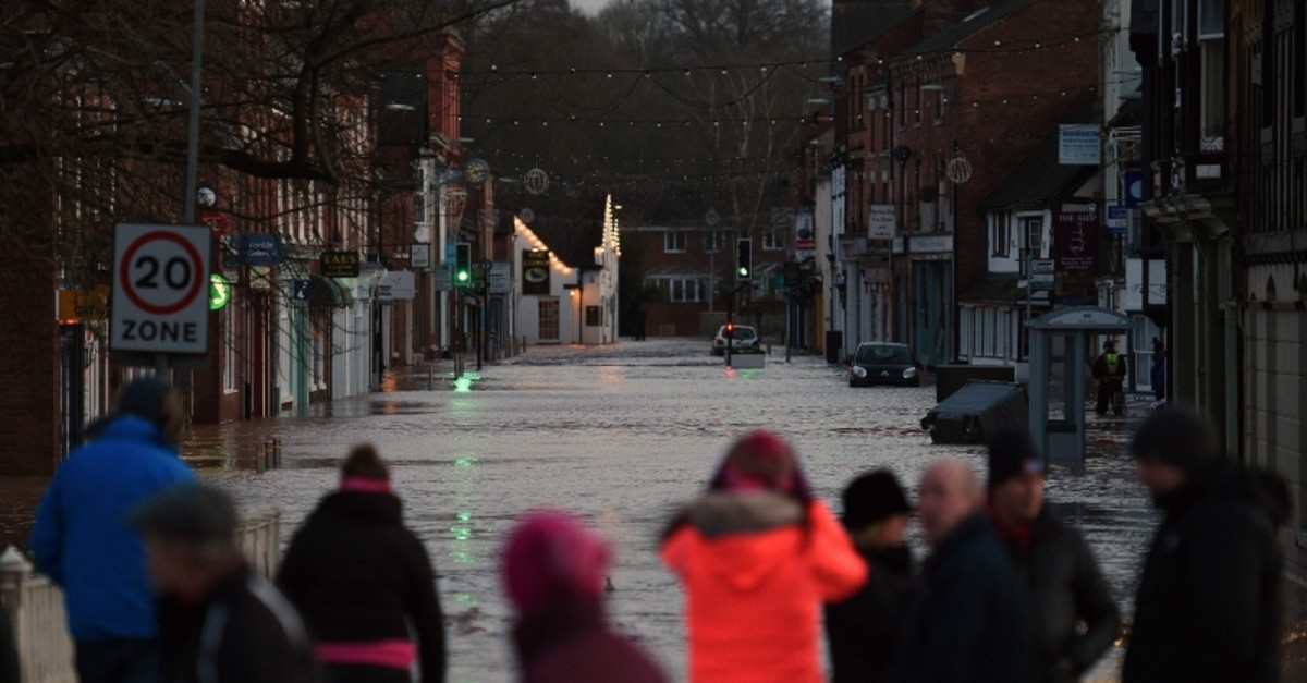 People look at flood water in a flooded street in Tenbury Wells, after the River Teme burst its banks in western England, on February 16, 2020, after Storm Dennis caused flooding across large swathes of Britain. (AFP Photo)