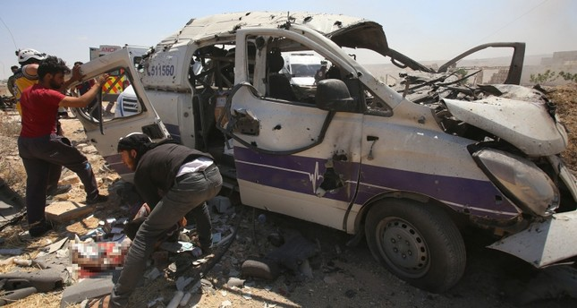 Syrian rescuers help a badly wounded man following a regime air strike which targeted an ambulance in the town of Maaret al-Numan in northwest Syria on June 20, 2019. (AFP Photo)