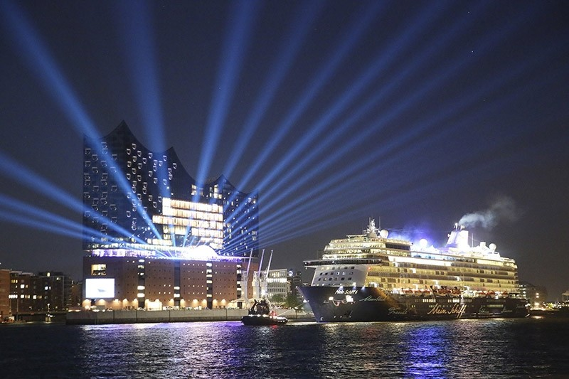 In this May 31, 2017 photo Cruise ship ,Mein Schiff 6, passes the Elbphilharmonie concert hall during a test run  in Hamburg, Germany. (AP Photo)