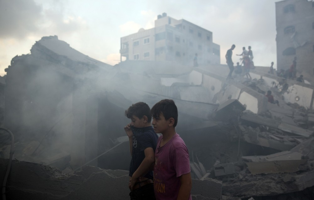 Palestinians inspect the damaged building of Said al-Mis'hal cultural center after it was hit by an Israeli airstrike, Gaza City, Aug. 9.