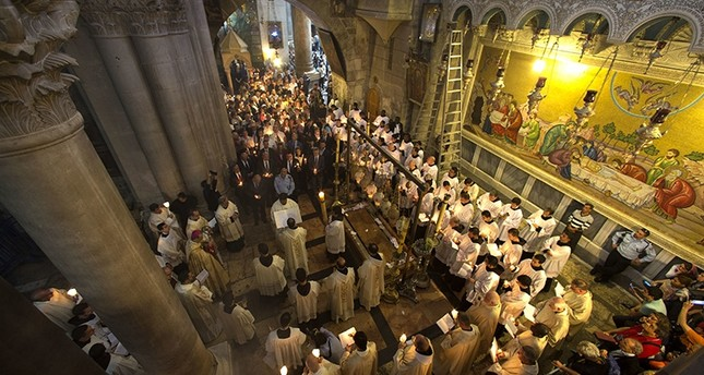 Christian clergymen hold candles during the Easter Sunday procession at the Church of the Holy Sepulchre, traditionally believed by many Christians to be the site of the crucifixion and burial of Jesus Christ, in Jerusalem, Sunday, April 16, 2017 (AP