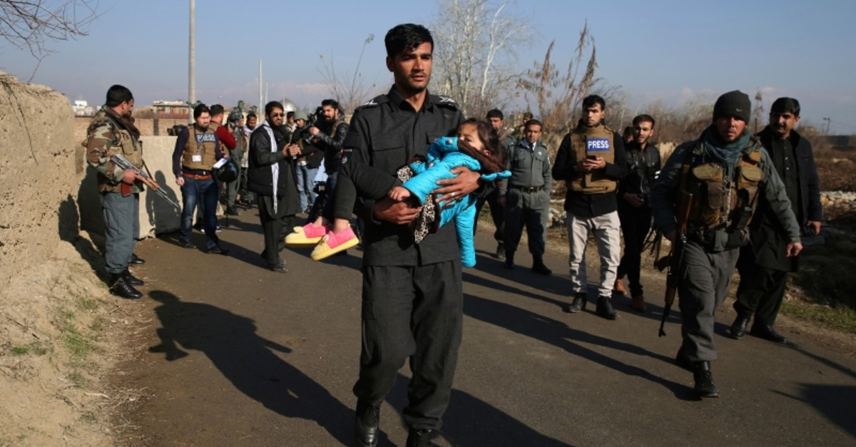 In this Dec. 11, 2019, photo, an Afghan Security police carries his injured daughter after an attack near the Bagram Air Base In Parwan province of Kabul, Afghanistan. (AP Photo)