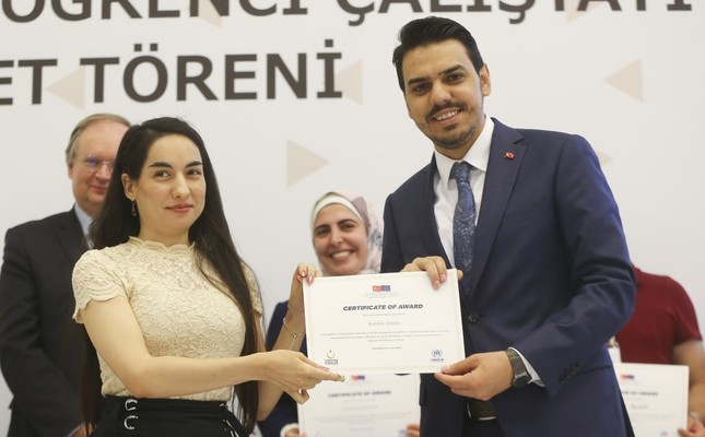 YTB chairman Abdullah Eren (right) gives a certificate to a newly graduated Syrian student at a ceremony in Ankara, July 4, 2019.