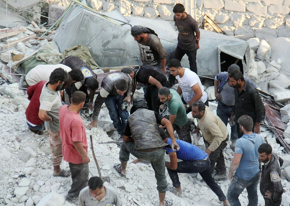 Residents and members of the Syrian Civil Defence, also known as White Helmets, search for victims in the northwestern town of Harim in Idlib province, on September 29, 2017. (AFP Photo)