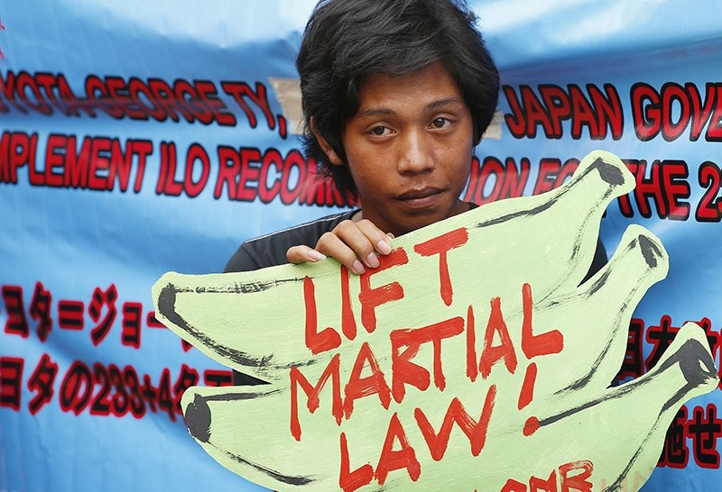 A protester holds a placard to protest the extension of martial law on Mindanao island in southern Philippines, July 18, 2017, in Manila, Philippines. (AP Photo)