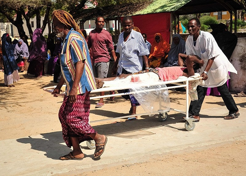 Somali men carry in a stretcher a man injured in the explosion of a truck bomb in the center of Mogadishu, Somalia, Oct. 15, 2017. (AFP Photo)
