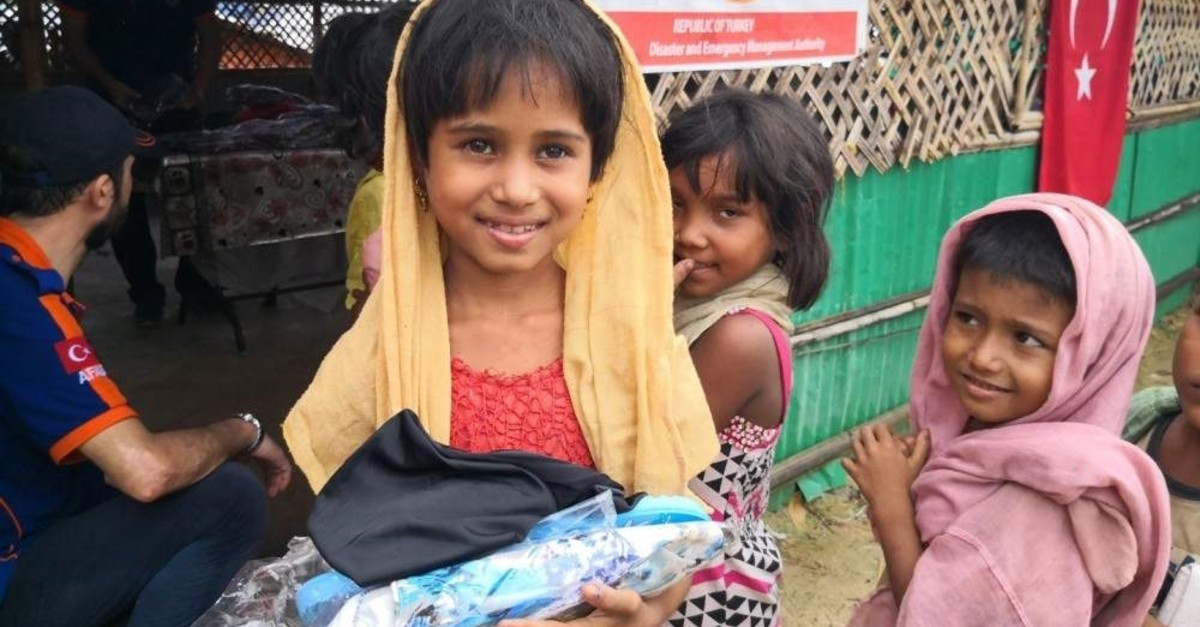 In this undated photo, a Rohingya girl smiles after receiving an aid package from AFAD at a camp for Rohingya Muslims in Bangladesh. (COURTESY OF AFAD)