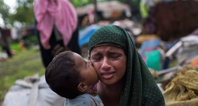 A Rohingya Muslim child places a kiss on his mother's cheek as they rest after having crossed over from Myanmar to the Bangladesh side of the border near Cox's Bazar's Teknaf area. (AP Photo)