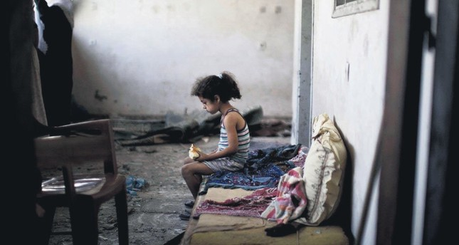 A Palestinian girl sits in the rubble of her destroyed home following an overnight Israeli airstrike on Gaza City, Aug. 2, 2014.