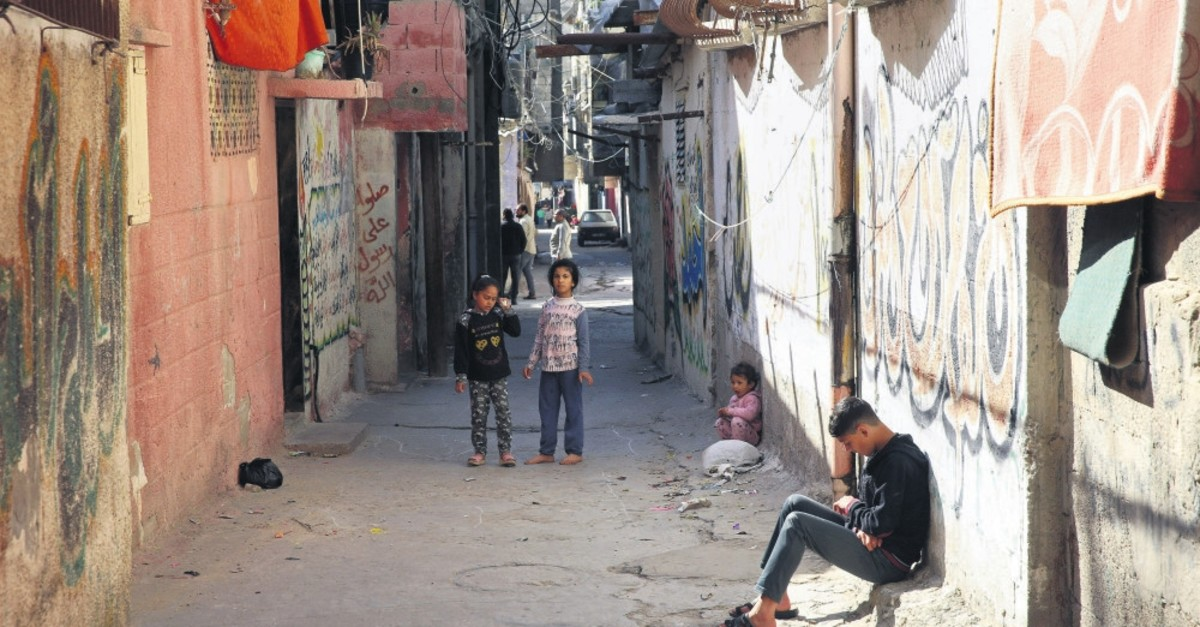 A Palestinian teenager sits in an alley as children play in front of their family house in the Shati refugee camp, Gaza City, April 21, 2019.