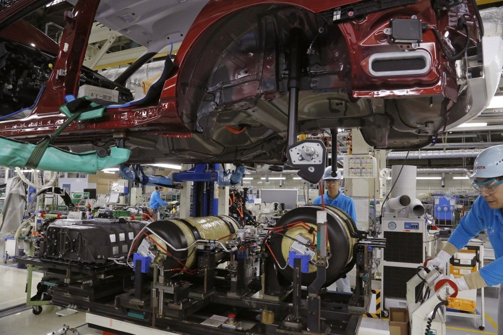 Workers of Toyota Motor Corp. assemble a Mirai fuel cell vehicle at the automaker's Motomachi plant in Toyota, western Japan.