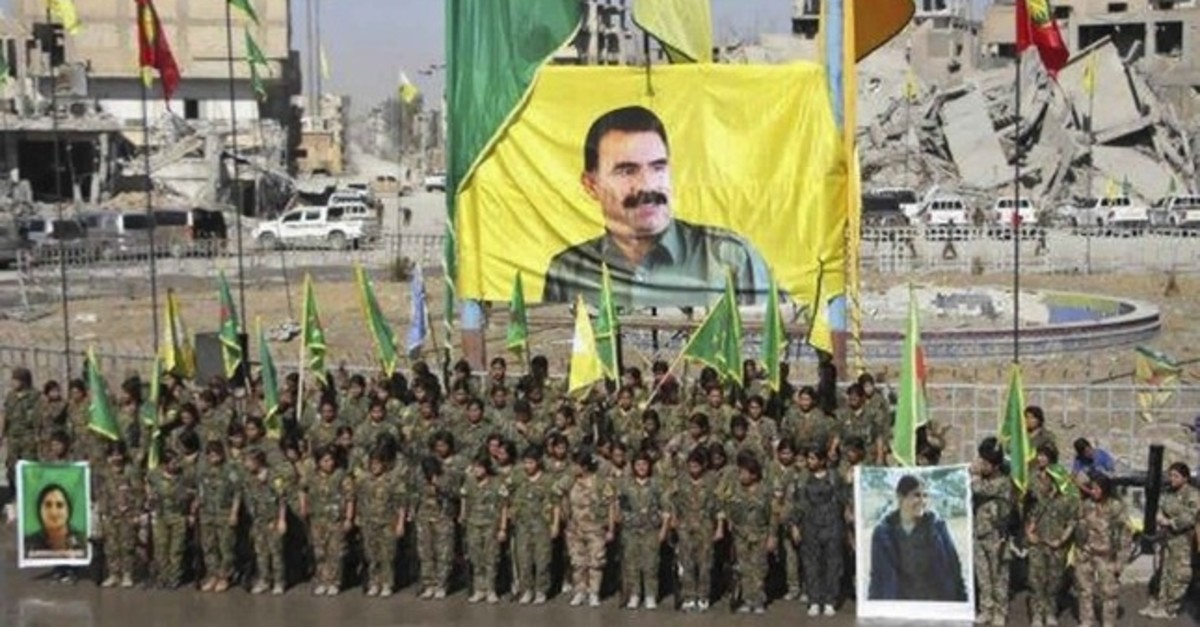 YPG members stand under a portrait of their PKK Abdullah u00d6calan, as they celebrate victory against Daesh in Raqqa, Syria. (AP Photo)