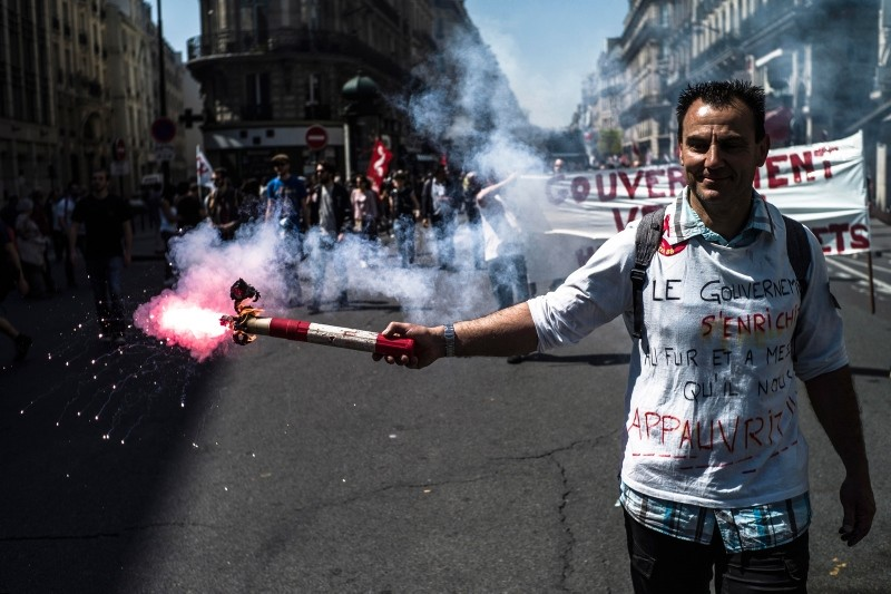 A protester lights a flare during a demonstration titled 'La fete a Macron' (Macron's party) against the policies of French President Emmanuel Macron (EPA Photo)