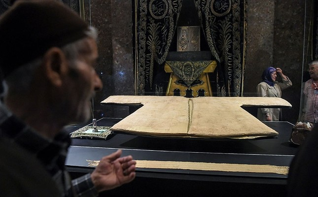People look at and offer prayers beside next to the sacred cloak of the Islamic Prophet Mohammed in a mosque on June 2, 2017 in Istanbul. (AFP Photo)