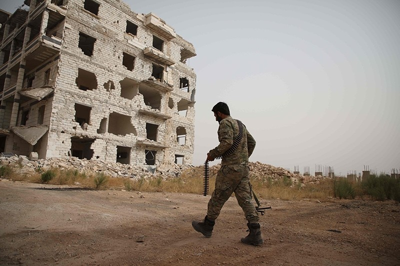 A Syrian opposition-fighter from the National Liberation Front (NLF) walks in a street in the opposition-held al-Rashidin district of western Aleppo's countryside near Idlib province, on Oct. 15, 2018. (AFP Photo)