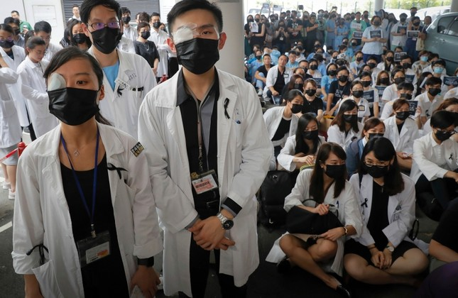 Medical staff wearing eyepatch and face masks take part in a protest against police brutality on the protesters, at a hospital in Hong Kong, Tuesday, Aug. 13, 2019. (AP Photo)