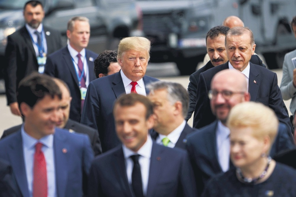 U.S. President Trump (L) and President Erdou011fan (R), with other leaders (front), go to take a family photo during the NATO Summit in Brussels, July 11.