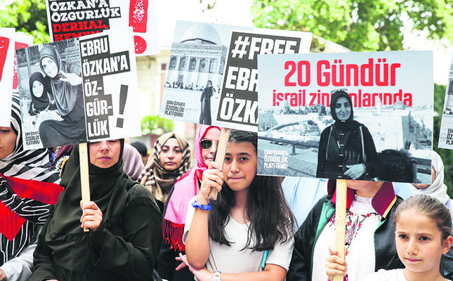 People hold placards with slogans reading Free Ebru Özkan and photos of Özkan during a rally calling for her release in Istanbul on June 30.