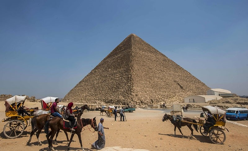 This file photo taken on August 31, 2016 shows Egyptians riding their carts past the Great Pyramid of Cheops, aka Pyramid of Khufu (AFP Photo)