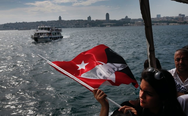 Aboard a boat crossing the Bosporus, separating Asia and Europe, a woman holds a Turkish flag decorated with a picture of Turkish Republic founder Mustafa Kemal Atatürk, Istanbul, June 16.