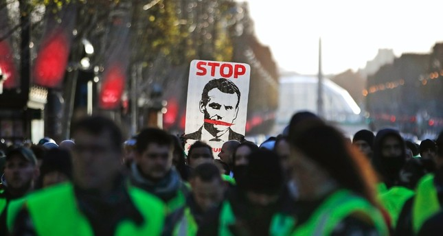 'Yellow vest' protesters hold a sign showing 'Stop Macron' as they walk down the Champs Elysees Avenue to Place de la Concorde during a demonstration in Paris, Dec. 8.