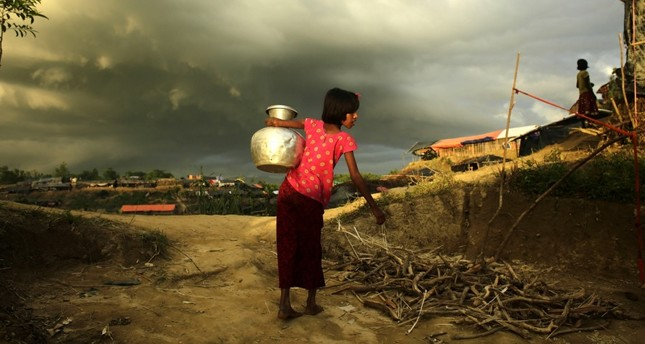 A Rohingya girl carries water to her family's makeshift tent in a camp in Cox's Bazar, Bangladesh, Oct. 5.