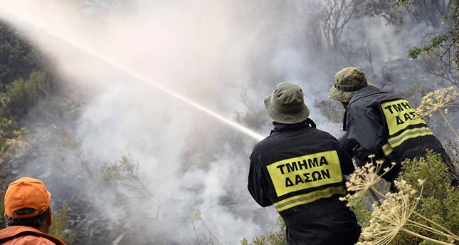 A Cypriot reservist volunteer firefighter (L) and members of the forest department battle fire on June 21, 2016 during a forest fire above the Cypriot village of Evrychou in the Troodos mountain area (AFP Photo)