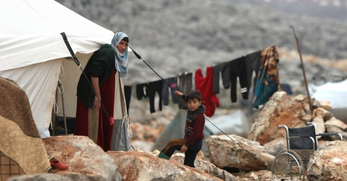 Syrians who fled pro-regime forces' attacks in Idlib and Aleppo provinces are pictured at a makeshift camp for displaced people on Feb. 18, 2020, north of the city of Idlib, near the Turkish border. (AFP Photo)