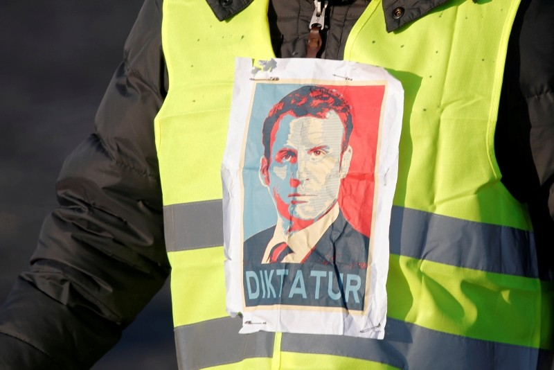 A man wearing a yellow vest, a symbol of a French drivers' protest against higher fuel prices, attends the demonstration with an image of French president Emmanuel Macron, in Paris, France, November 17, 2018. (Reuters Photo)