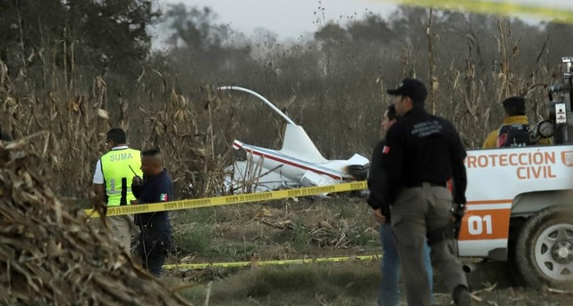 Police and rescue personnel stand at the scene where the helicopter transporting Martha Erika Alonso, governor of the state of Puebla, and his husband Senator Rafel Moreno Valle crashed, in Coronango, Puebla Mexico, December 24, 2018. (Reuters Photo)