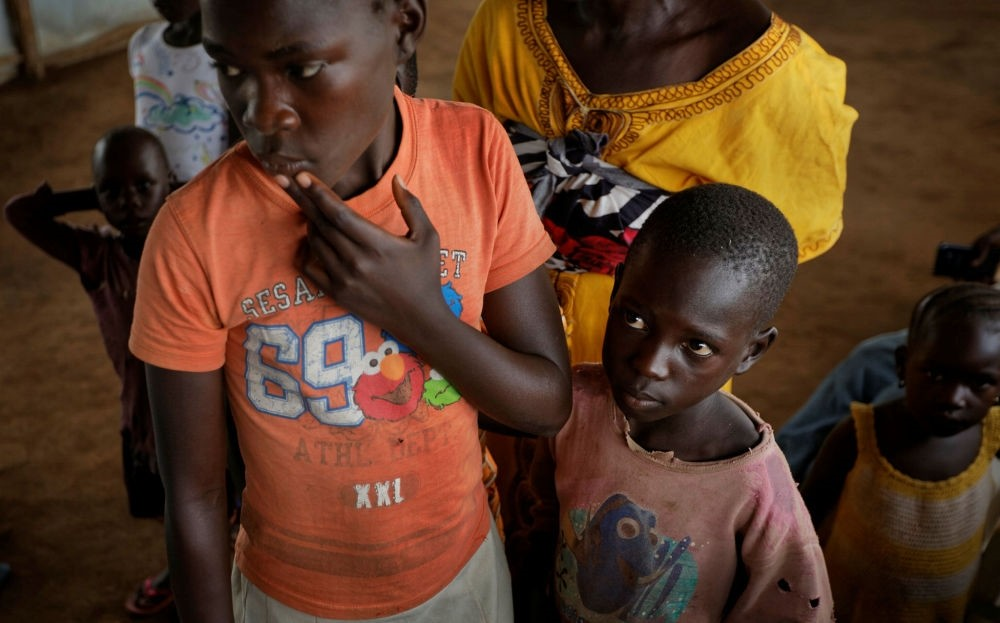Unaccompanied South Sudanese refugee children line up to have their details recorded before being taken to a refugee transit center, in Kuluba, northern Uganda.