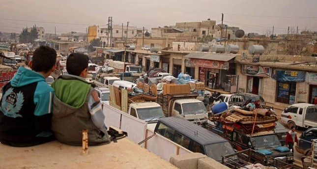 Syrian boys sit on a ledge and watch traffic in the town of Hazano in the northern countryside of Idlib, as people flee northwards in vehicles transporting their belongings, amid an ongoing regime offensive, Feb. 4, 2020. AFP Photo