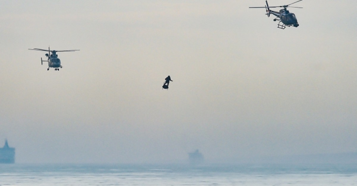Franky Zapata stands on his jet-powered ,flyboard, next to helicopters as he arrives at St. Margaret's Bay in Dover, on August 4, 2019. (AFP Photo)
