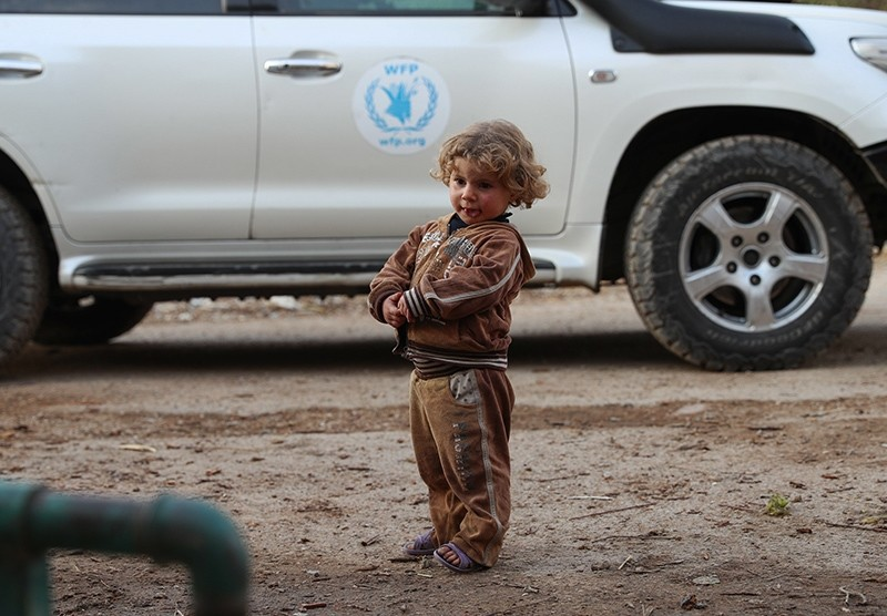 A child stands next to a World Food Program (WFP) vehicle which is part of a humanitarian operation in al-Nishabieh area in Eastern Ghouta in rural Damascus, Syria, Nov. 28, 2017. (EPA Photo)