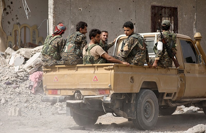 Fighters from Syrian Democratic Forces (SDF), which is dominated by the PKK terrorist group's Syrian offshoot, sit on the back of a pick-up truck in Raqqa, Syria, Sept. 25, 2017. (Reuters Photo)