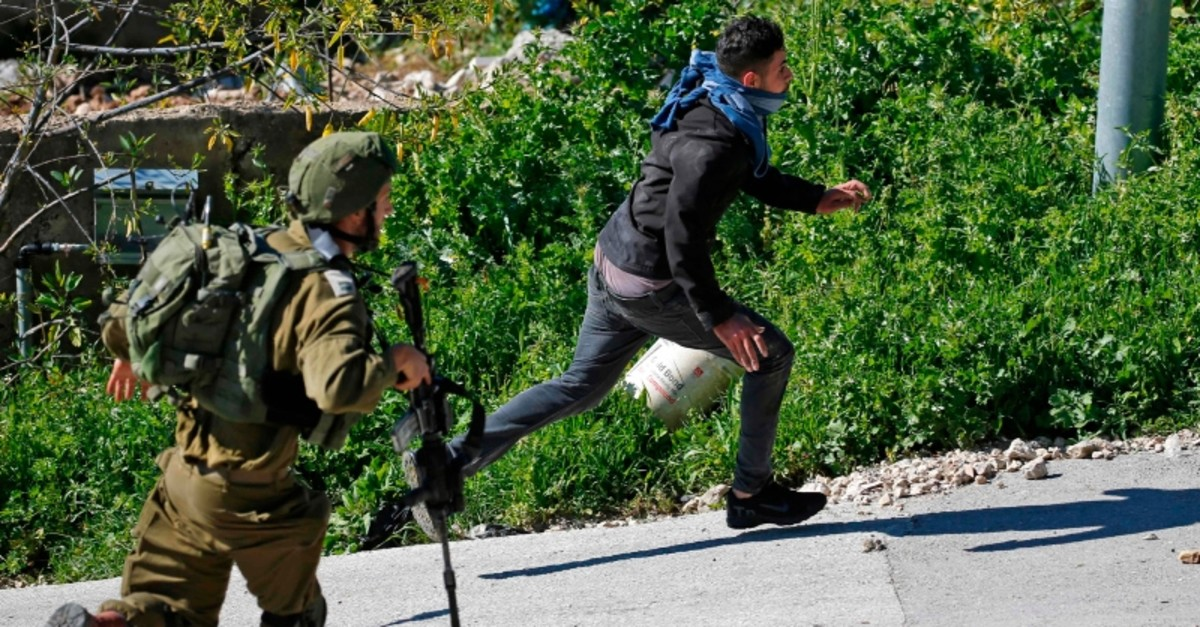An Israeli soldier chases a Palestinian protester during clashes following a demonstration against Jewish settlements in the Israeli-occupied West Bank village of Beit Sira, west of Ramallah, March 8, 2019. (AFP Photo)
