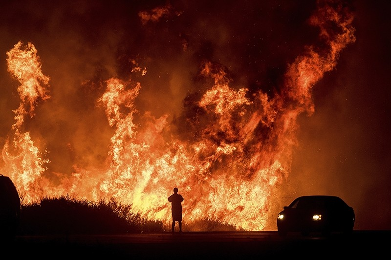 A motorists on Highway 101 watches flames from the Thomas fire leap above the roadway north of Ventura, Calif., on Dec. 6, 2017. (AP Photo)