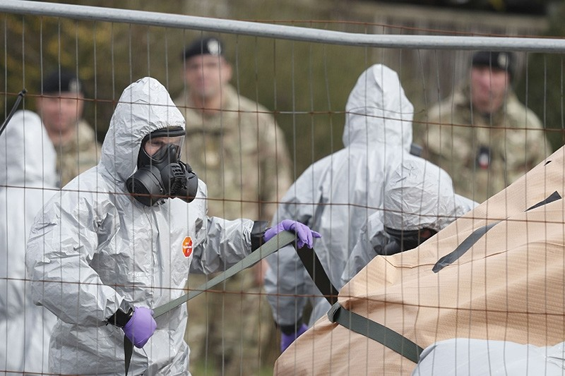 In this file photo taken on March 14, 2018 British military personnel wearing protective coveralls work to remove a vehicle connected to the March 4 nerve agent attack in Salisbury from a residential street in Gillingham, England. (AFP Photo)