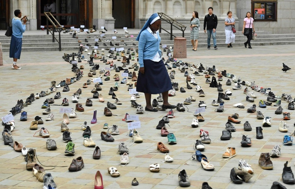 Catholic Agency For Overseas Development's (CAFOD) Sister Clara from Zambia, walks through shoes displayed outside Westminster Cathedral, London, Aug. 15.