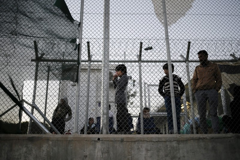 A migrant child stands next to a metal fence at the Moria refugee camp on the Greek island of Lesbos, November 5, 2015. (Reuters Photo)
