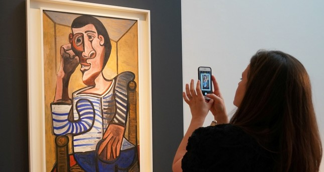 In this file photo taken on May 3, 2018 a Christie's employee takes a picture of Pablo Picasso's Le Marin during a media preview at Christie's in New York. (AFP Photo)