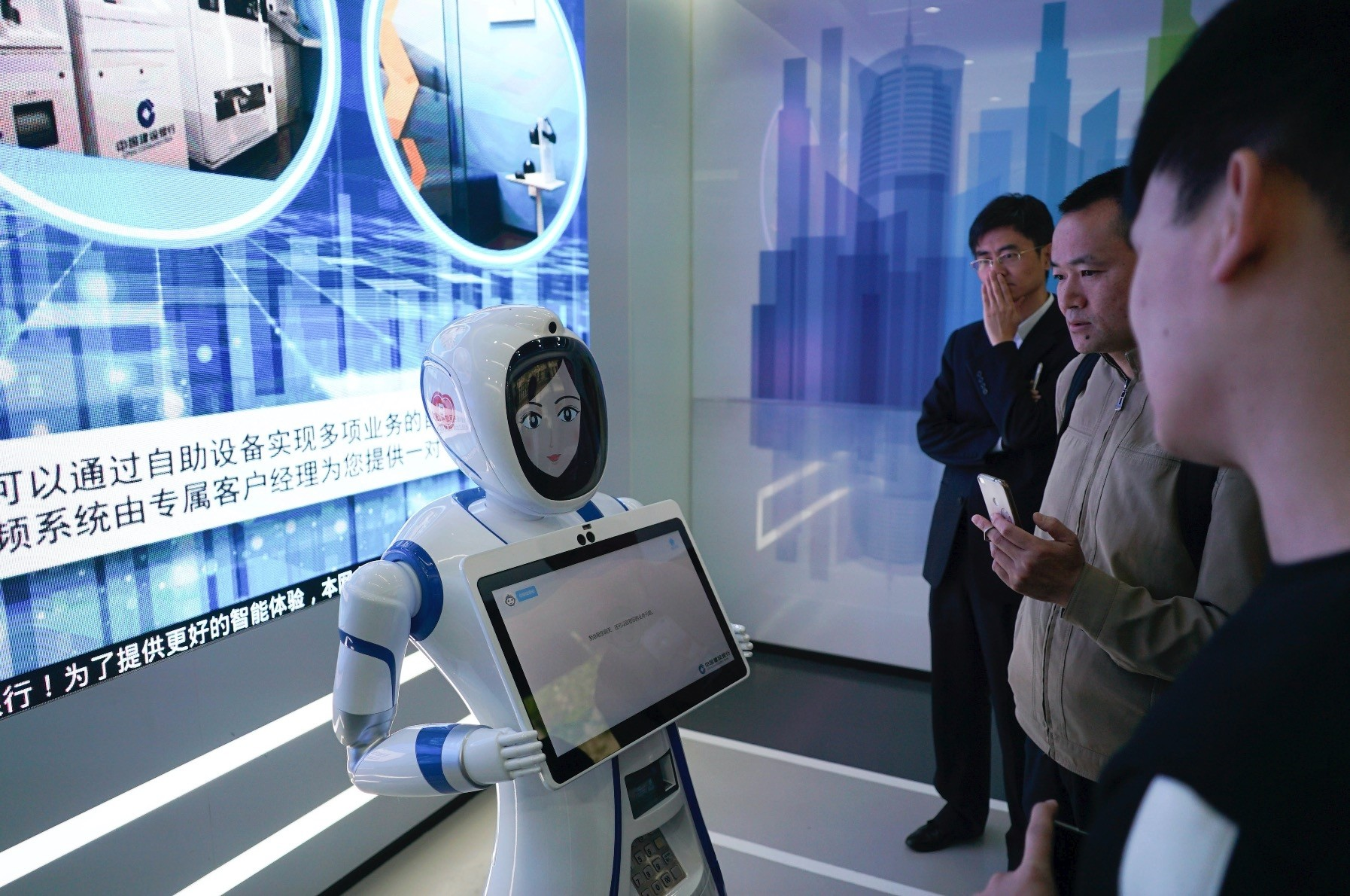 Bank customers speak with a robot at an automated branch in Shanghai.