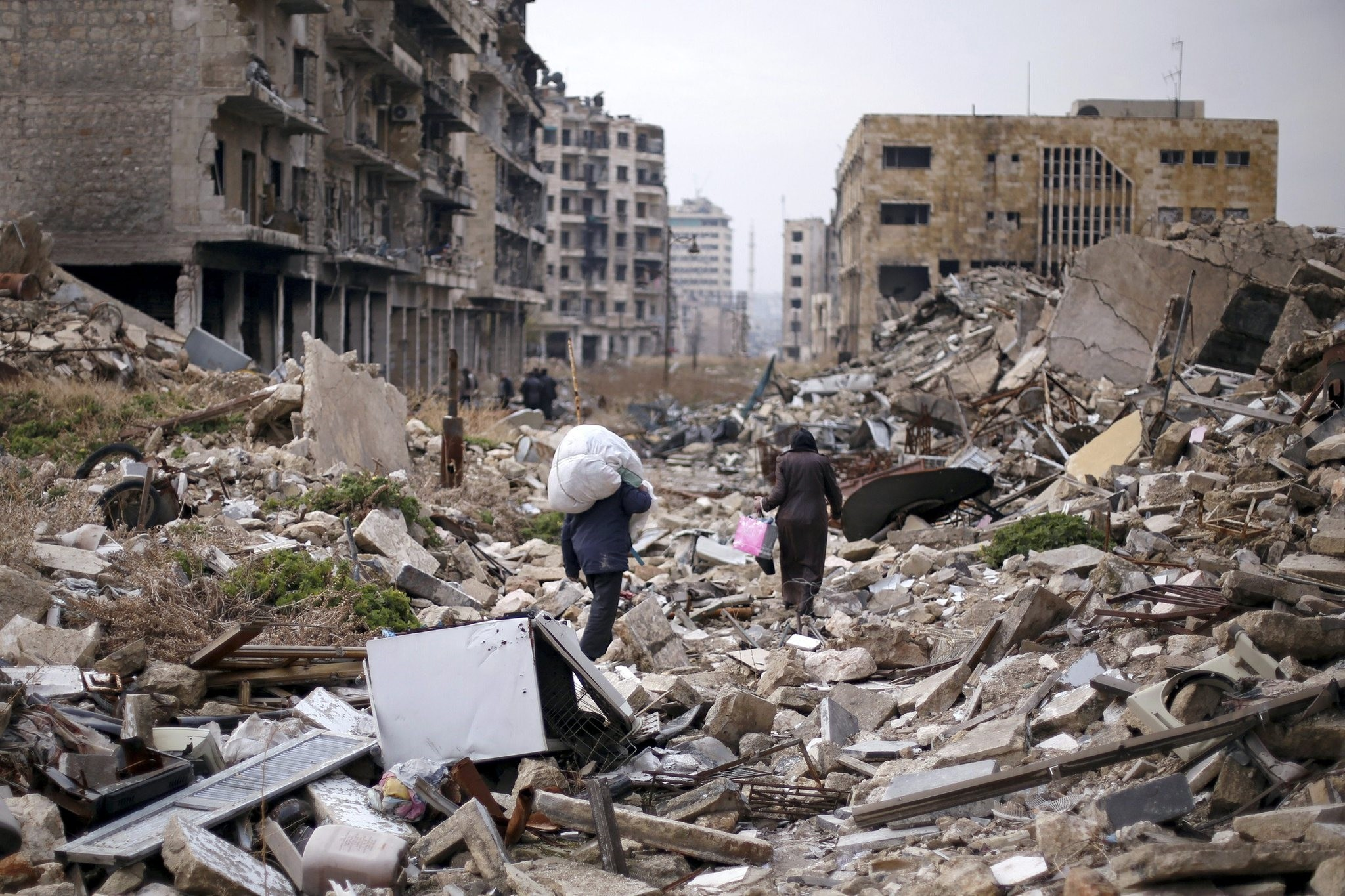 People walk amid the rubble as they carry belongings that they collected from their houses in the regime controlled area of Aleppo, Syria December 17, 2016. (Reuters Photo)