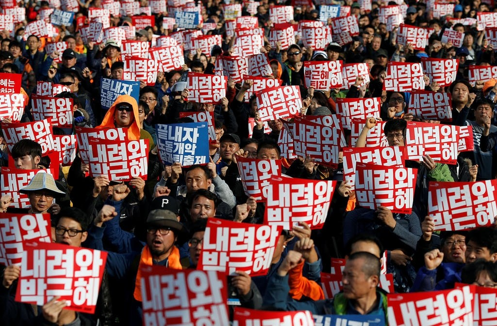 People chant slogans during a rally calling for President Park Geun-hye to step down in central Seoul. The placards read, Step down Park Geun-hye. Reuters Photo