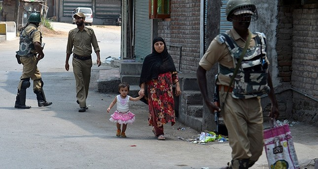 Indian paramilitary troopers patrol as a Kashmiri woman with a child walks during a curfew in Srinagar on August 5, 2016. (AFP Photo)