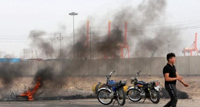 An Iraqi protester walks past a burning tire as protestors block the entrance to Umm Qasr Port, Basra, Nov. 7, 2019. (Reuters Photo)