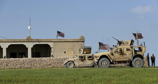 U.S. soldiers sit on a house that has been turned into an outpost on a road leading to the tense front line between U.S.-backed YPG terrorists and Turkish-backed fighters, Halawanji village, north of Manbij town, Syria, March 29.