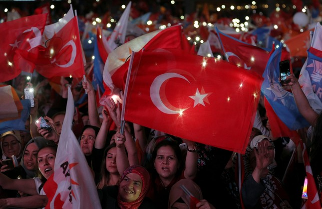 AK Party supporters wave flags to celebrate the June 24 results in front of their party's headquarters, Ankara, June 24.