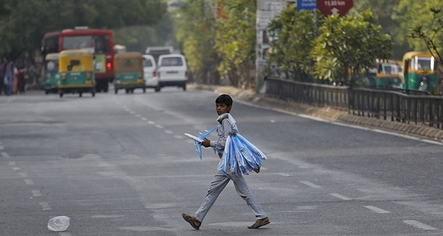 An Indian boy who sells toy planes at a traffic intersection reacts to camera as he crosses a road on the eve of World Day Against Child Labor in Ahmadabad (AP Photo)