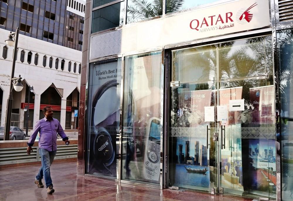 A man passes the closed office of Qatar Airways in King Fahad Road, Riyadh, Saudi Arabia, June 6. -